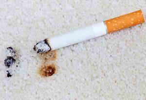 Zigarettenfleck auf Teppich